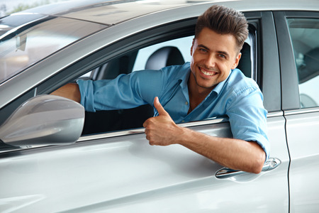 dream car: Car Showroom. Hombre feliz en el interior del coche de su sueño.