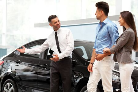 ar: Сar Salesman Invites Customers at Showroom.