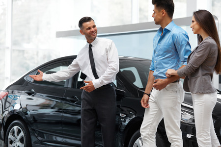 car salesperson: Car Salesman Invites Customers at Showroom.