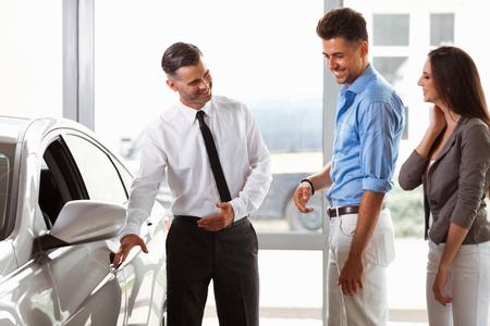 familias felices: Exposición de coches. Pareja joven comprar un coche nuevo en la concesionaria.