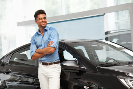 selling service smile: Car Showroom. Happy Man near Car of His Dream.