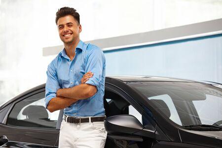 dream car: Car Showroom. Hombre feliz cerca del coche de su sueño.