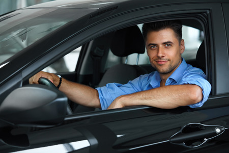 Car Showroom. Happy Man inside Car of His Dream.