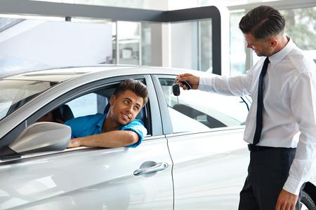 handing over: Car Salesman Handing over new Car Key to Customer at Showroom Stock Photo