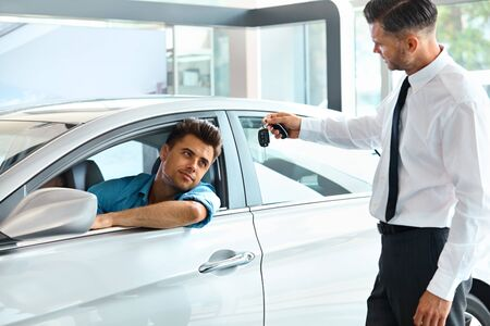 car rent: Car Salesman Handing over new Car Key to Customer at Showroom Stock Photo