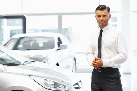 Verkoper die zich in autoopslag bevinden. Auto showroom.