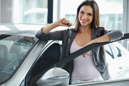 new cars: Woman Driver Holding Car Keys. Car Showroom.