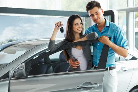 Het jonge paar vieren Aankoop van een auto In Auto Showroom