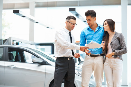 car salesperson: Young Couple Signing a Contract in Car Showroom. Stock Photo