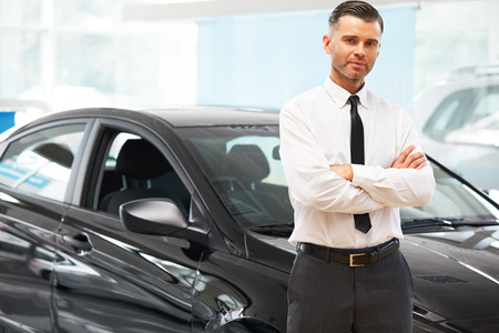 car salesperson: Salesman Stands Near Brand New Car. Car Showroom