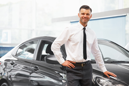 car salesperson: Salesman standing in car retail store. Car Showroom.