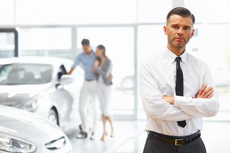 Salesman debout en magasin voiture de détail. Salle d'exposition pour voitures.