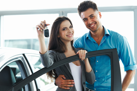 purchases: Young Couple Celebrating Purchase of a car In Car Showroom