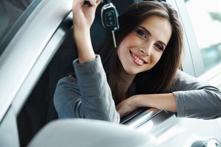 Kobieta kierowca trzyma klucze do samochodu umiejscowienia w swoim nowym samochodem.