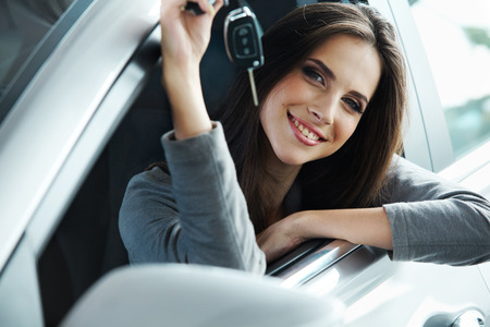 rent: Woman Driver Holding Car Keys siting in Her New Car. Stock Photo