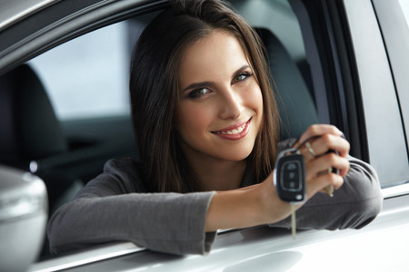 siting: Woman Driver Holding Car Keys siting in Her New Car. Stock Photo