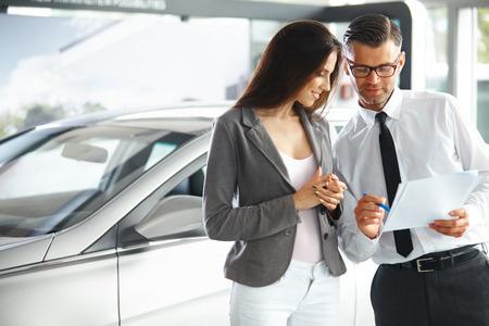 Jeunes Documents femme de signature chez le concessionnaire de voiture avec Salesman Banque d'images - 40140750
