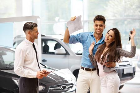 젊은 부부는 자동차 쇼룸에서 자동차의 구매를 축하 스톡 콘텐츠