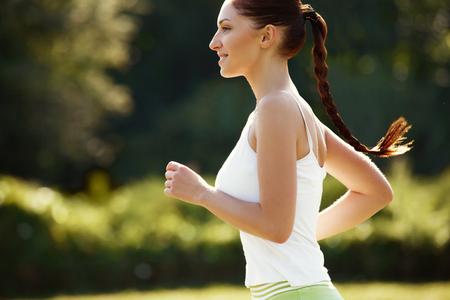 Athletic Runner Training in a park for Marathon. Fitness Girl Running outdoors 版權商用圖片