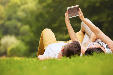 person computer: Couple in summer park using electronic tablet