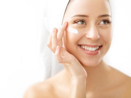 Retrato de la hermosa mujer de aplicar la crema en la cara - aislados en blanco