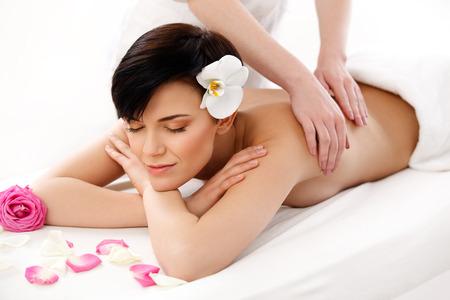 Spa Treatment. Beautiful Woman Getting Stones Massage in Spa Salon. photo
