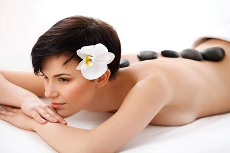 relax massage: Spa Treatment. Beautiful Woman Getting Stones Massage in Spa Salon.