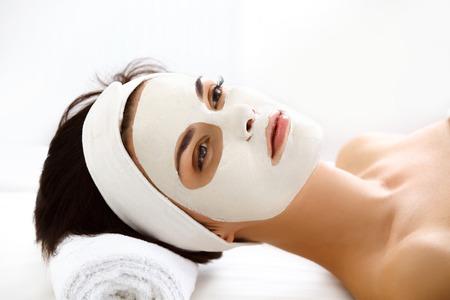 mujer maquillandose: Mujer hermosa con la máscara cosmética en cara. Chica Obtiene Tratamiento en Spa Salon contra el fondo blanco Foto de archivo