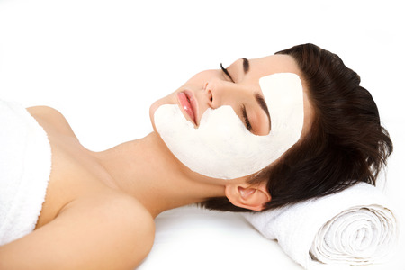 Beautiful Woman With Cosmetic Mask on Face. Girl Gets Beauty Treatment in Spa Salon against white Background Stock Photo