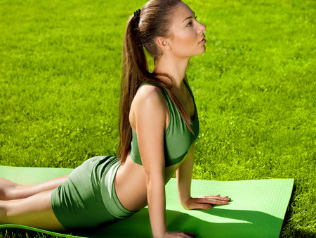 A beautiful sporty woman doing stretching exercise against nature background