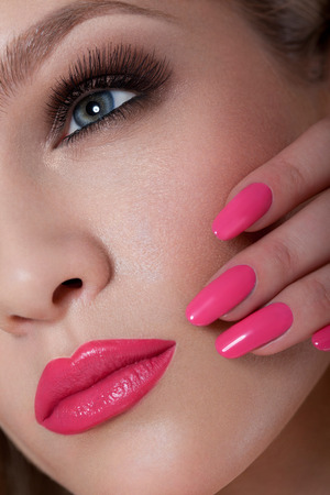 pink nail polish: Manicure and Makeup. Beautiful Woman With Pink Nails and Luxury Makeup. Red Sexy Lips and Long Eyelashes