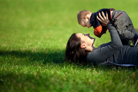 newborn baby mother: Happy family. A young mother and baby playing Stock Photo