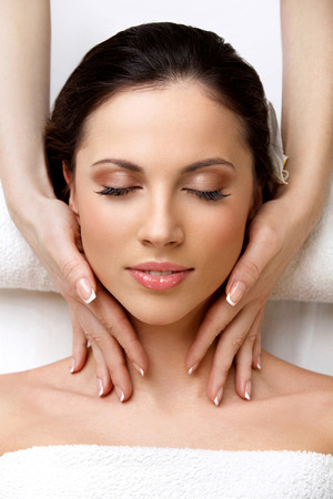 Spa Woman. Close-up of a Beautiful Woman Getting Spa Treatment in Spa Salon. Face Massage photo