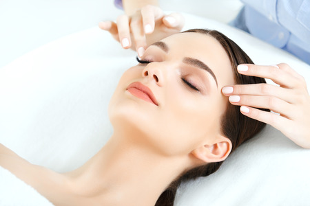 facial cleansing: Face Massage. Close-up of a Young Woman Getting Spa Treatment.