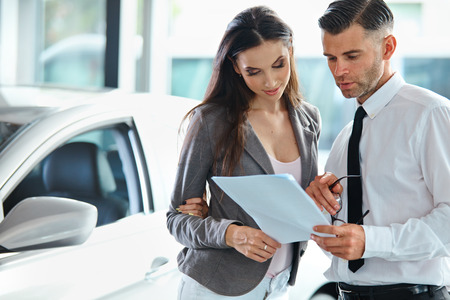 buying a car: Young Woman Signing Documents at Car Dealership with Salesman Stock Photo