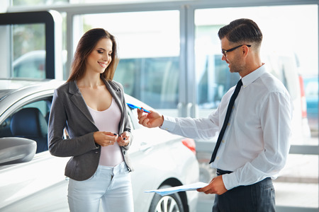 dealership: Young Woman Signing Documents at Car Dealership with Salesman Stock Photo