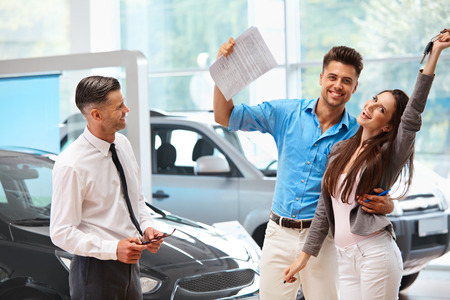 purchase: Young Couple Celebrating Purchase of a car In Car Showroom