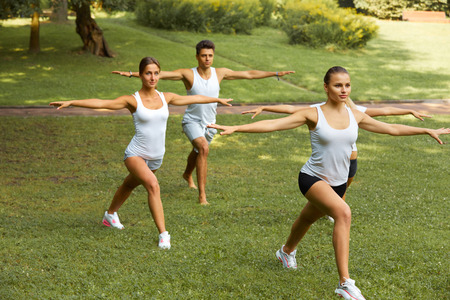 woman stretching: Fitness class. Portrait of smiling people doing power fitness exercise at summer park