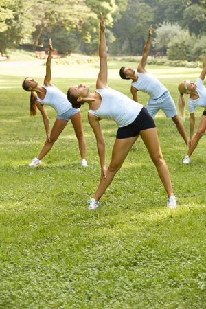 outdoor fitness: Fitness class. Portrait of smiling people doing power fitness exercise at summer park