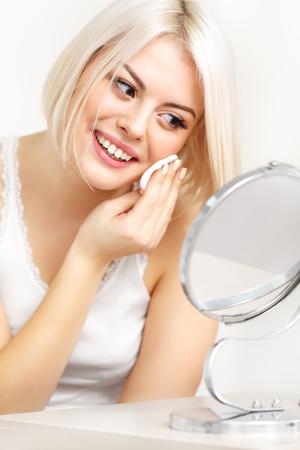 miror: Makeup Applying. Beautiful Woman Looking at Her Face in the Miror applying cosmetic sponge