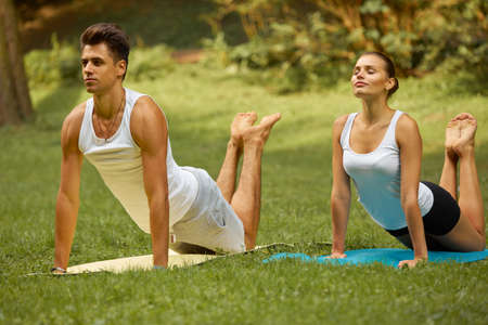 healthy men: Yoga Exercise. Young couple meditating in Summer Park Stock Photo