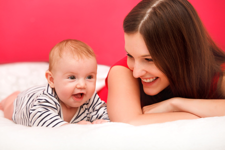 children laughing: Baby and Mother playing.  Happy Smiling Family Portrait
