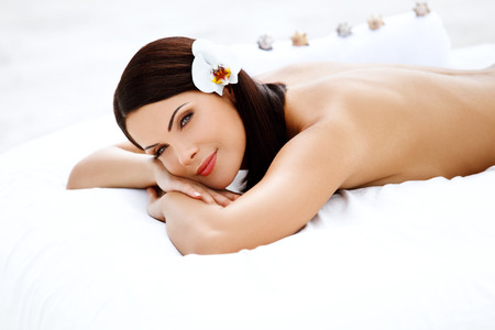 lying on back: Spa Woman. Beautiful Young Woman Relaxing After Massage. Spa salon.