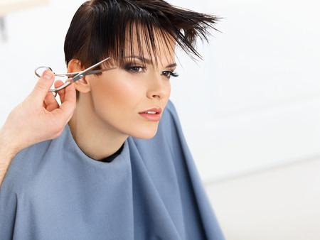 haircutting: Brown Hair. Hairdresser Cutting Womans Hair in Beauty Salon. Haircut. Hairstyle Stock Photo
