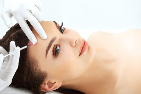 lift hands: Beautiful woman gets botox injections. Cosmetology. Beauty Face