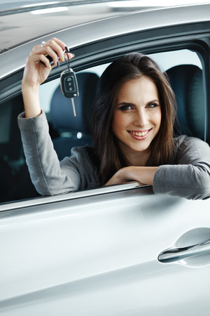 rental: Woman Driver Holding Car Keys siting in Her New Car. Stock Photo