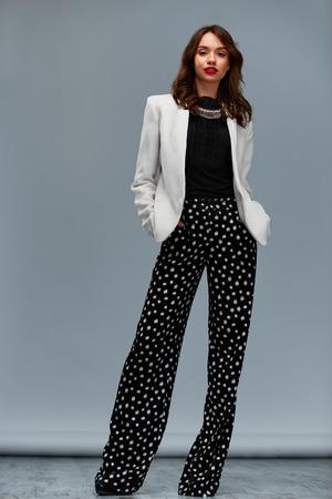 moda ropa: A la moda del retrato. Presentaci�n de la muchacha con las manos en los bolsillos, con ropa elegante estilo. Foto de archivo