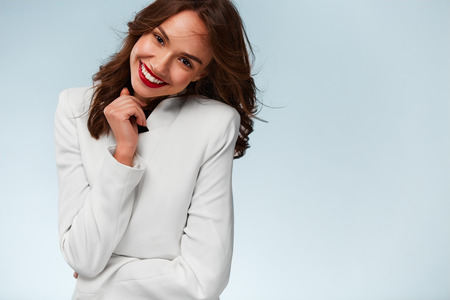 front teeth: Attractive female portrait. Beautiful young woman with healthy white teeth wearing white jacket and  smiling at the camera. White background. Stock Photo
