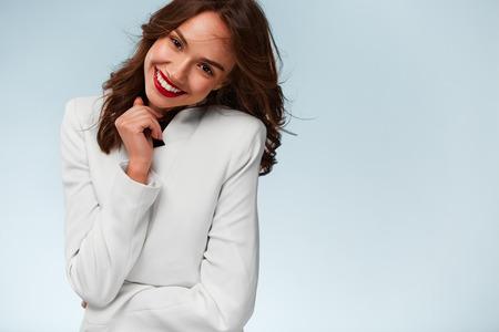Portrait de femme Attractive. Belle jeune femme avec des dents blanches saines portant la veste blanche et souriant à la caméra. Fond blanc. Banque d'images - 45680527