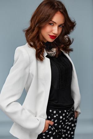 Retrato de una mujer hermosa de moda confidentes positivas de visita elegante de pie con las manos en los bolsillos y sonriendo a la cámara Foto de archivo